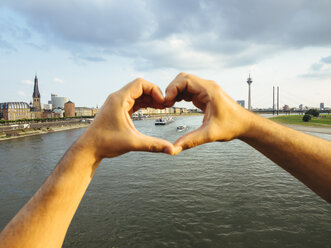 Germany, Duesseldorf, hands forming a heart framing ships on Rhine River - KRPF01933