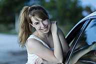 Smiling woman leaning against car, portrait - SHKF00707