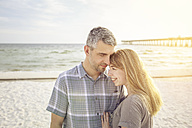 USA, Kissing couple sitting at Panama City Beach - SHKF00713