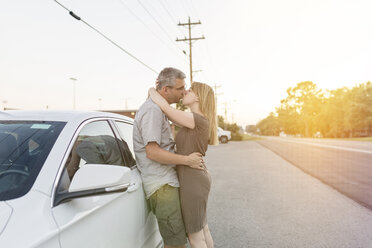 Couple on a road trip taking a break kissing each other - SHKF00719