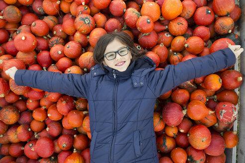 Portrait os smiling girl lying on pile of Hokkaido pumpkins - LVF05516
