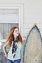 Redheaded young woman with surfboard in front of facade - RORF00370