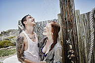 Young couple taking shower on the beach with clothes - RORF00379
