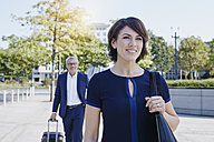 Smiling businesswoman on the go with businessman in background - RORF00386