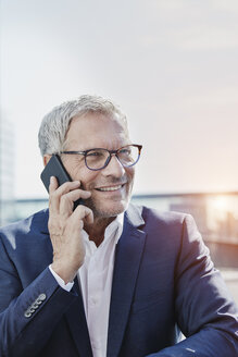 Smiling businessman on cell phone outdoors - RORF00401