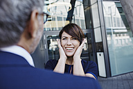 Excited woman looking at businessman - RORF00422