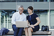 Businessman and businesswoman sitting on bench sharing laptop - RORF00425