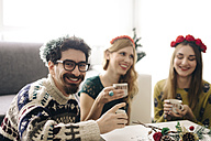 Portrait of smiling man relaxing with friends at Christmas time - LCUF00067