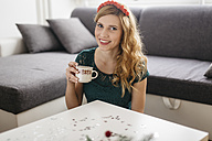 Portrait of smiling young woman drinking coffee at home at Christmas time - LCUF00070