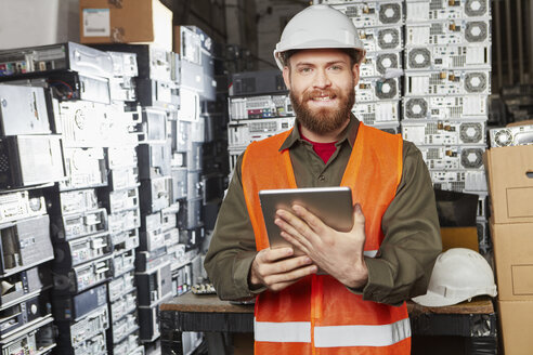 Worker in computer recycling plant using digital tablet - RKNF00410