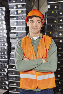 Worker in computer recycling plant, portrait - RKNF00413