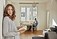 Woman with book leaning against wall at home - FMKF03132