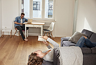 Couple relaxing with book and laptop at home - FMKF03135