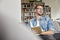 Laughing man sitting with book on couch in the living room - FMKF03138
