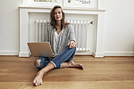 Smiling woman sitting on the floor  with laptop - FMKF03141