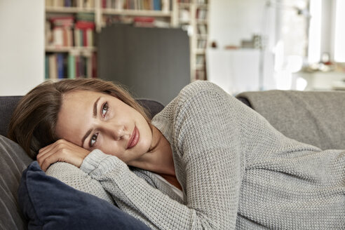 Portrait of young woman relaxing on couch in the living room - FMKF03144