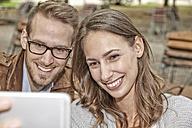 Portrait of happy couple taking selfie with smartphone in autumnal beer garden - FMKF03156