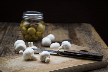 Fresh white champignon and pocket knife on wooden board and glass of pickled champignons - LVF05554