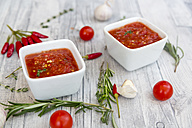 Two bowls of homemade tomato sauce and ingredients on wood - SARF03050