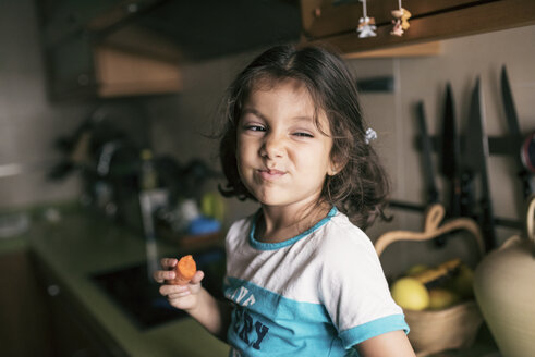 Portrait of little girl pulling funny face while eating a carrot - JASF01277