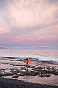 Spain, Tenerife, boy carrying surfboard on the beach at sunset - SIPF01006