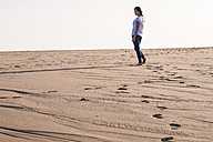 Young woman walking in sand on the beach - SIPF01010