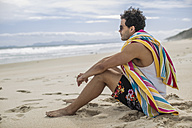 Young man sitting on the beach - ZEF11301