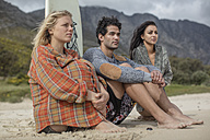 Friends with surfboard sitting together on the beach - ZEF11313