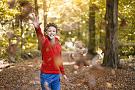 Smiling boy throwing leaves in the air in the autumnal forest - DIGF01398