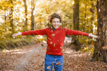 Smiling boy throwing leaves in the air in the autumnal forest - DIGF01401