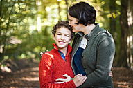 Portrait of smiling boy with his mother arm in arm in the autumnal forest - DIGF01419