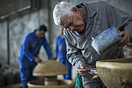 Man working on ceramics in industrial pot factory - ZEF11385