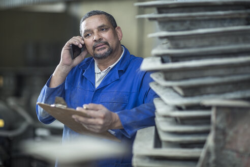 Man with clipboard on the phone in a factory - ZEF11388