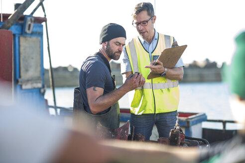 Fisherman on trawler talking to inspector - ZEF11409