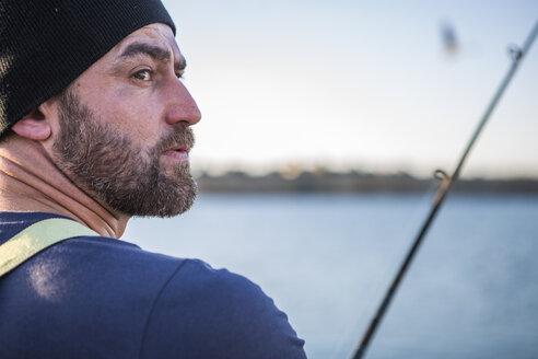 Fisherman catching fish with fishing rod - ZEF11415