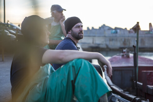 Fishermen sitting in harbour at sunset - ZEF11421