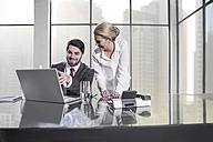 Businessman and woman in meeting discussing in office, using laptop - ZEF11466