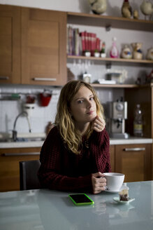 Portrait of woman sitting in the kitchen with cup of tea - MAUF00857