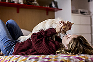 Woman lying on bed playing with her dog - MAUF00866