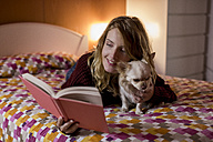 Smiling woman lying on bed with her dog reading a book - MAUF00869