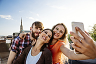 Austria, Vienna, three friends taking selfie on rooftop terrace with Stephansdom in the background - AIF00414