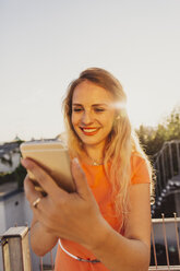 Portrait of smiling blond woman taking selfie on rooftop terrace with at backlight - AIF00417