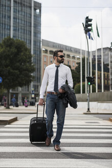 Businessman with suitcase crossing the street - MAUF00881