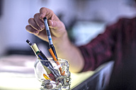 Man's hand taking pencil, close-up - ZEF11475
