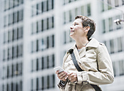 USA, New York City, smiling woman in Manhattan with cell phone - UUF08941