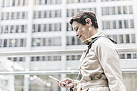 USA, New York City, smiling businesswoman on the go with cell phone and earphones - UUF08956