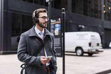 USA, New York City, businessman with cell phone and headphones on the go - UUF08965