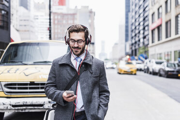 USA, New York City, businessman with cell phone and headphones on the go - UUF08968