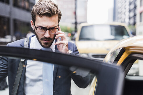 USA, New York City, businessman in Manhattan on cell phone entering a taxi - UUF08971
