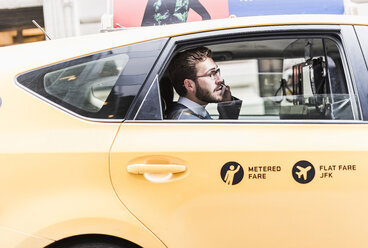 USA, New York City, businessman on cell phone in a taxi - UUF08974